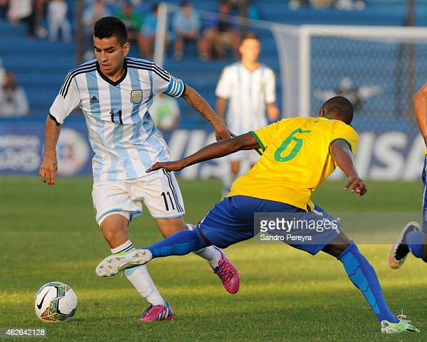 Ángel Correa of Argentina drives the ball as Caju of Brazil tries to stop him during a match between Argentina and Brazil as part of South American...