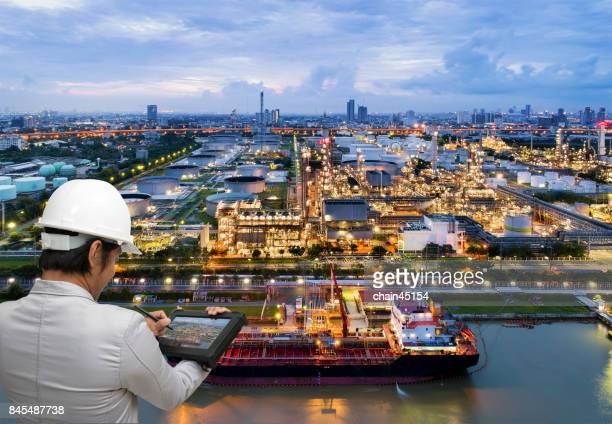 ngineer hold tablet to mangae business of Oil refinery industry plant from aerial view in oil refinery industry or oil industrial. This oil refinery is in the city for refinery producing of oil and gasoline. Industrial concept.