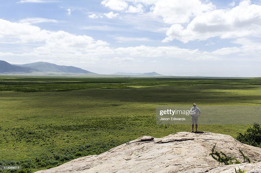 A tourist surveys the vast and endless African savannah from a granite kopje.