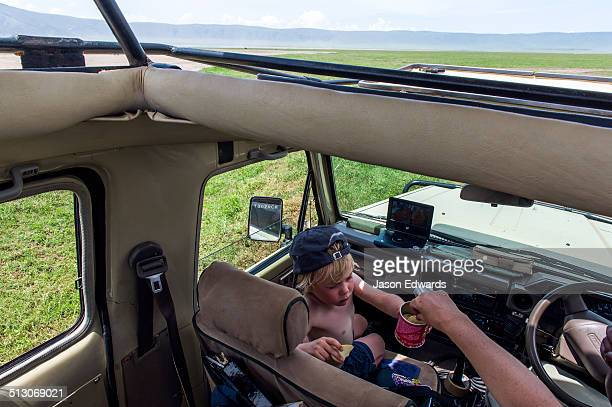 A boy shares potato chips with his mother whilst on safari on the savannah.