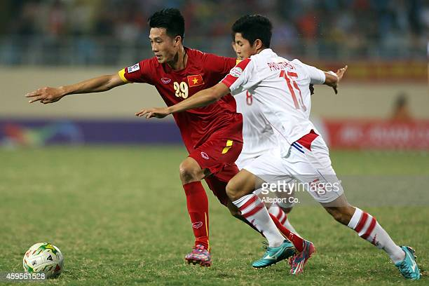 Nguyen Huy Hung of Vietnam battles with Phoutthasay Khochalern of Laos during the 2014 AFF Suzuki Cup Group A match between Laos and Vietnam at the...