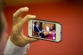 Nguyen Tan Dung Vietnam's prime minister is seen on a Apple Inc iPhone 4s smartphone during an interview in Hanoi Vietnam on Friday May 30 2014...