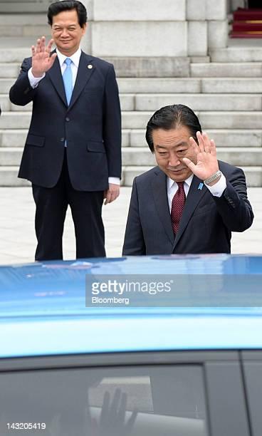 Nguyen Tan Dung Vietnam's prime minister left and Yoshihiko Noda Japan's prime minister wave during a demonstration of a Nissan Motor Co Leaf...