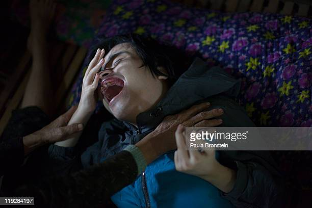 Nguyen Van Chuoi cries for his mother suffering from severe mental and physical disabilities March 7 in Cam Lo Quang Tri district Vietnam and like...