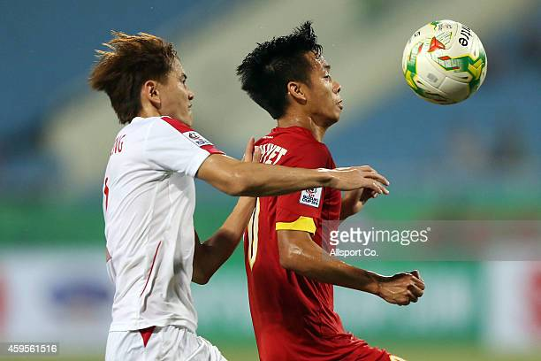 Nguyen Van Quyet of Vietnam battles with KSaison of Laos during the 2014 AFF Suzuki Cup Group A match between Laos and Vietnam at the My Dinh Stadium...
