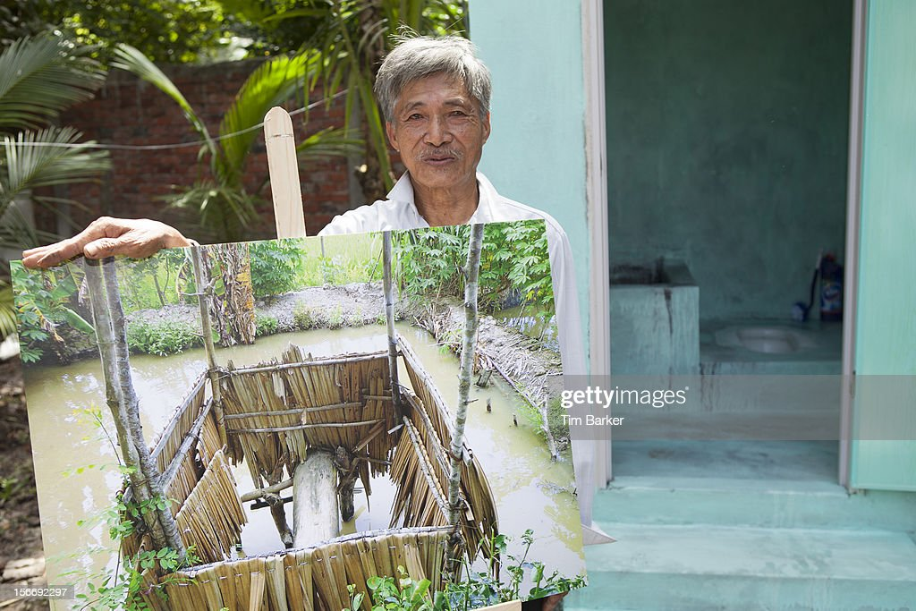 Nguyen Van Tu displays a picture of his old toilet as he poses in front of his newly installed toilet as part of a media briefing for World Toilet Day on November 19, 2012 in Vinh Long, Vietnam.