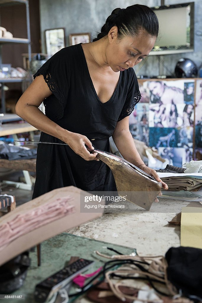 Ni Luh Ayu Pertami, the designer and the owner of Niluh Djelantik measures a wooden shoelast at her atelier on November 12, 2013 in Canggu Village, Bali, Indonesia. Niluh Djelantik (formerly called Nilou), the hand made high end leather shoe, is produced by Balinese shoe lover and designer Ni Luh Ayu Pertami with 40 shoes designers and workers in a small atelier at Canggu Village. This brand signature by a unique engraving and designed to be comfortable high heels or wedges with elegan touch. Celebrities like Cate Blanchett, Uma Thurman, Julia Roberts, Paris Hilton, Cameron Diaz and American top model Gisele Bundchen have been known to purchase Niluh Djelantik beautiful shoes and sandals.
