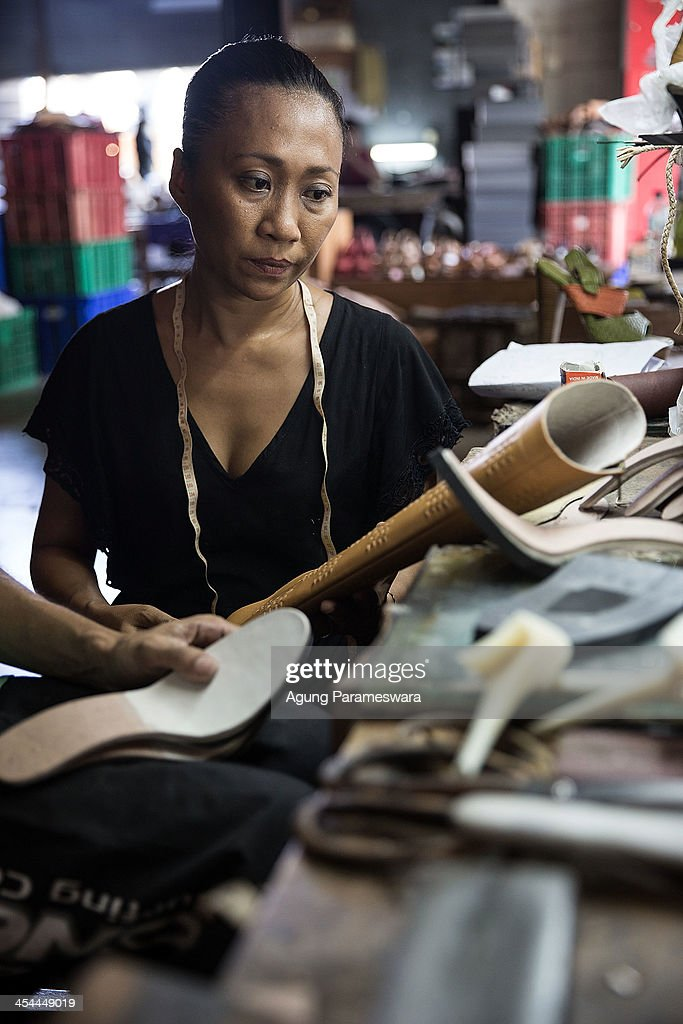 Ni Luh Ayu Pertami, the designer and the owner of Niluh Djelantik checks an unfinished boot shoe at her atelier on November 12, 2013 in Canggu Village, Bali, Indonesia. Niluh Djelantik (formerly called Nilou), the hand made high end leather shoe, is produced by Balinese shoe lover and designer Ni Luh Ayu Pertami with 40 shoes designers and workers in a small atelier at Canggu Village. This brand signature by a unique engraving and designed to be comfortable high heels or wedges with elegan touch. Celebrities like Cate Blanchett, Uma Thurman, Julia Roberts, Paris Hilton, Cameron Diaz and American top model Gisele Bundchen have been known to purchase Niluh Djelantik beautiful shoes and sandals.