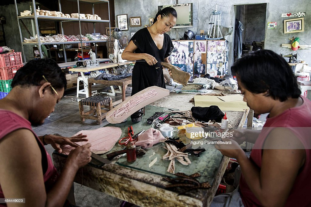 Ni Luh Ayu Pertami (C), the designer and the owner of Niluh Djelantik and staffs work at her atelier on November 12, 2013 in Canggu Village, Bali, Indonesia. Niluh Djelantik (formerly called Nilou), the hand made high end leather shoe, is produced by Balinese shoe lover and designer Ni Luh Ayu Pertami with 40 shoes designers and workers in a small atelier at Canggu Village. This brand signature by a unique engraving and designed to be comfortable high heels or wedges with elegan touch. Celebrities like Cate Blanchett, Uma Thurman, Julia Roberts, Paris Hilton, Cameron Diaz and American top model Gisele Bundchen have been known to purchase Niluh Djelantik beautiful shoes and sandals.