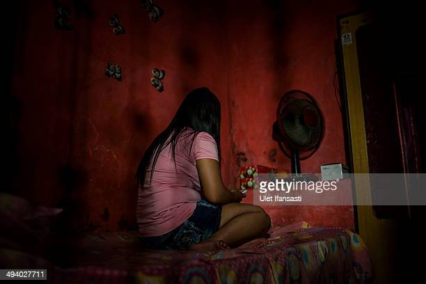 Nia a commercial sex worker woman sits inside her room at 'Jarak' brothel complex near 'Dolly' on May 25 2014 in Surabaya Indonesia She has worked as...
