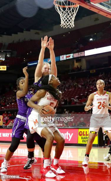 Niagara Purple Eagles guard Jai Moore and forward Kaylee Stroemple block Maryland Terrapins guard Kaila Charles during a women's college basketball...