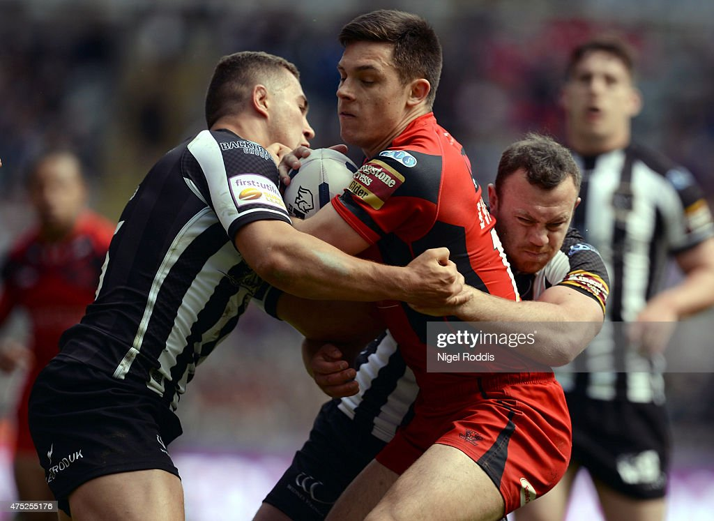 Niall Evalds (C) of Salford Red Devils challenged by Jack Owens (L) and Stefan Marsh of Widnes Vikings during the Super League match between Salford Red Devils and Widnes Vikings at St James' Park on May 30, 2015 in Newcastle upon Tyne, England.
