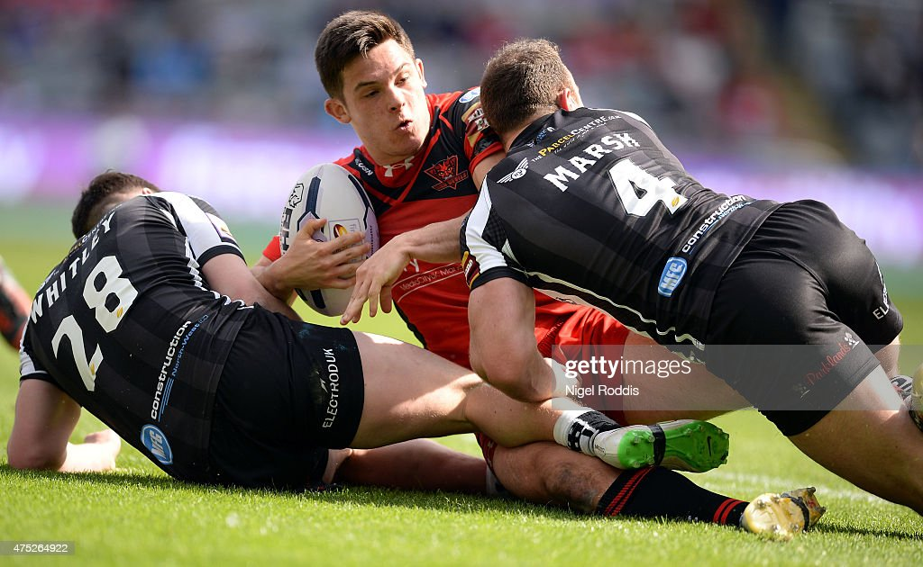 Niall Evalds (C) of Salford Red Devils challenged by Matt Whitley (L) and Stefan Marsh of Widnes Vikings during the Super League match between Salford Red Devils and Widnes Vikings at St James' Park on May 30, 2015 in Newcastle upon Tyne, England.
