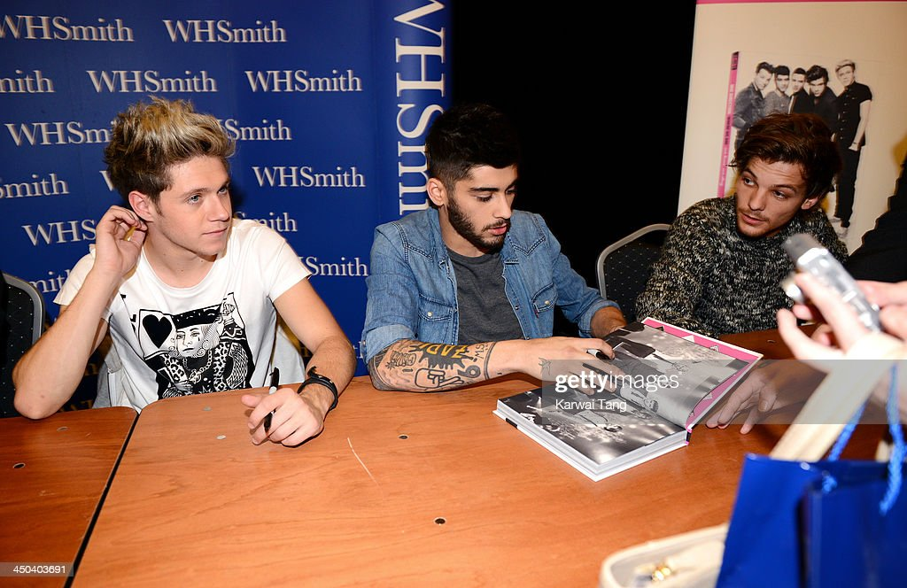Niall Horan, Zayn Malik and Louis Tomlinson of One Direction attend the book signing of One Direction's new book 'Where We Are' held at Alexandra Palace on November 18, 2013 in London, England.