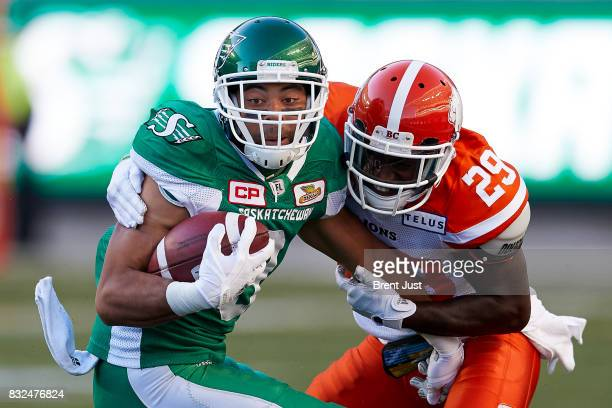 Nic Demski of the Saskatchewan Roughriders tries to escape the grasp of Steven Clarke of the BC Lions in the game between the BC Lions and the...