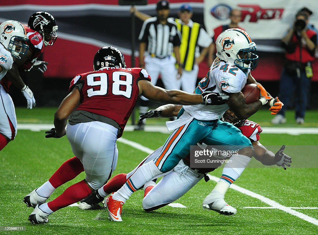 Nic Grigsby #42 of the Miami Dolphins carries the ball against Cliff Matthews #98 of the Atlanta Flacons during a preseason game at the Georgia Dome on August 12, 2011 in Atlanta, Georgia.