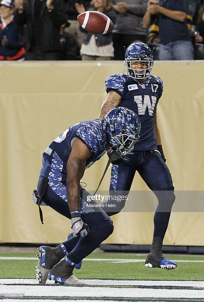 Nic Grigsby #32 of the Winnipeg Blue Bombers celebrates his touchdown as teammate Nick Moore #17 looks on in fourth quarter action in a CFL game against the Montreal Alouettes at Investors Group Field on August 22, 2014 in Winnipeg, Manitoba, Canada.