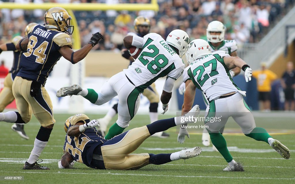 Nic Grigsby #32 of the Winnipeg Blue Bombers gets caught up with Mark LeGree #28 of the Saskatchewan Roughriders in first half action in a CFL game at Investors Group Field on August 7, 2014 in Winnipeg, Manitoba, Canada.