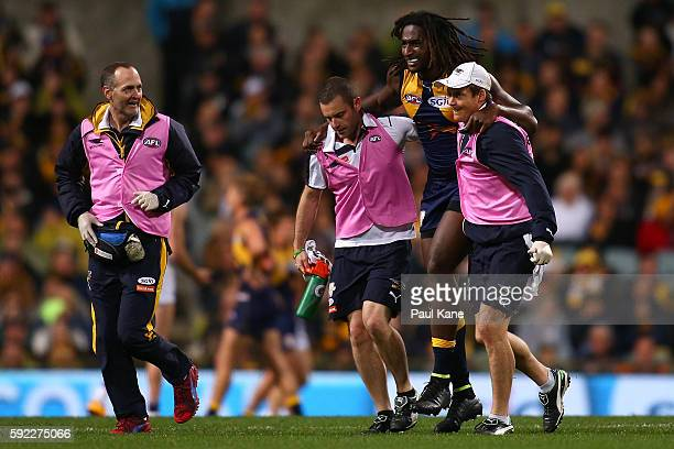 Nic Naitanui of the Eagles is assisted from the field with a knee injury during the round 22 AFL match between the West Coast Eagles and the Hawthorn...