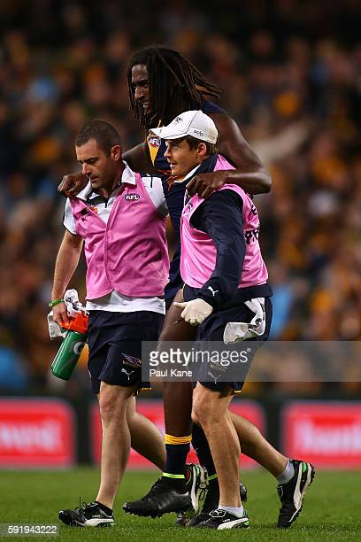 Nic Naitanui of the Eagles is assisted from the field with a leg injury during the round 22 AFL match between the West Coast Eagles and the Hawthorn...