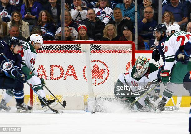 Nic Petan and Mathieu Perreault of the Winnipeg Jets battle Jared Spurgeon and Ryan Suter as they eye the loose puck in the crease in front of...