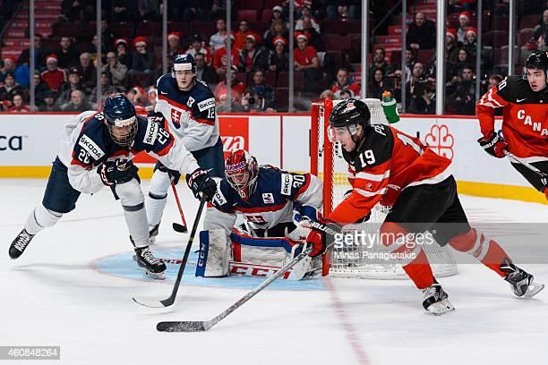 Nic Petan of Team Canada wraps around the net of goaltender Denis Godla of Team Slovakia during the 2015 IIHF World Junior Hockey Championship game...