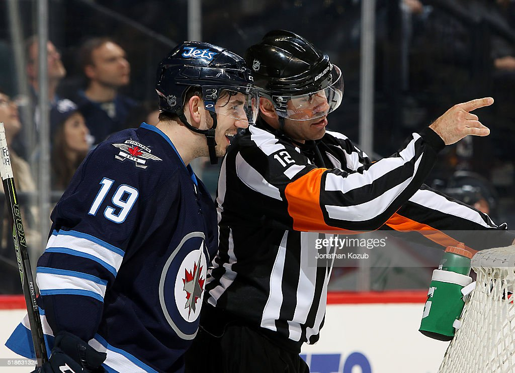 Nic Petan #19 of the Winnipeg Jets has a laugh as he chats with referee Justin St. Pierre #12 during a second period stoppage in play against the Chicago Blackhawks at the MTS Centre on April 1, 2016 in Winnipeg, Manitoba, Canada.