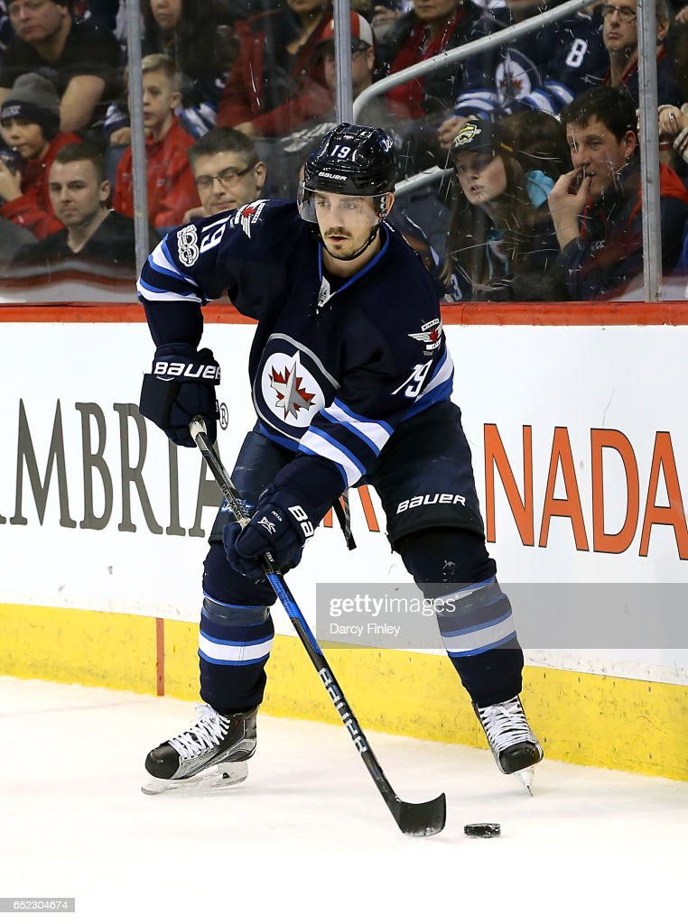 Nic Petan #19 of the Winnipeg Jets plays the puck along the boards during third period action against the Calgary Flames at the MTS Centre on March 11, 2017 in Winnipeg, Manitoba, Canada.