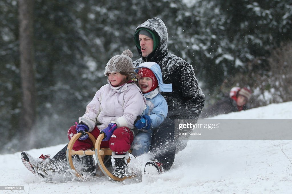 Nic rides a sled down a hill with his children Mischa and Janosch at a snow-covered park in Zehlendorf district on December 9, 2012 in Berlin, Germany. Northeastern Germany was inundated with a heavy snowfall that covered highways and blanketed the region with heavy snow.