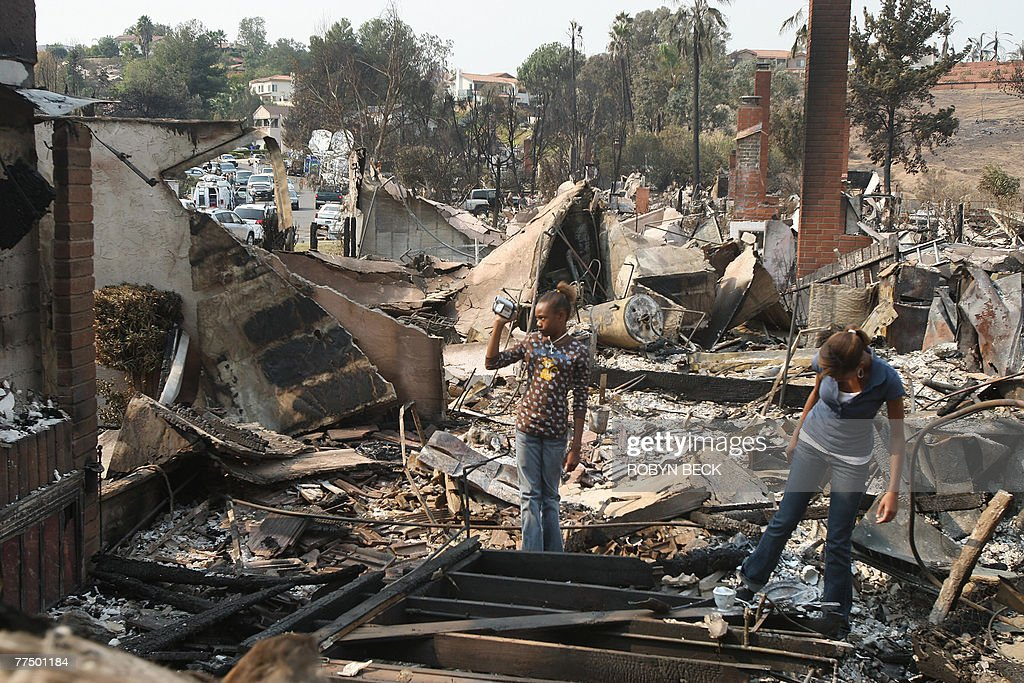 Nicaela Gilmore takes video as her sister Ashlee Gilmore searches for recoverable items in her family's home which was destroyed in the Witch Fire in...