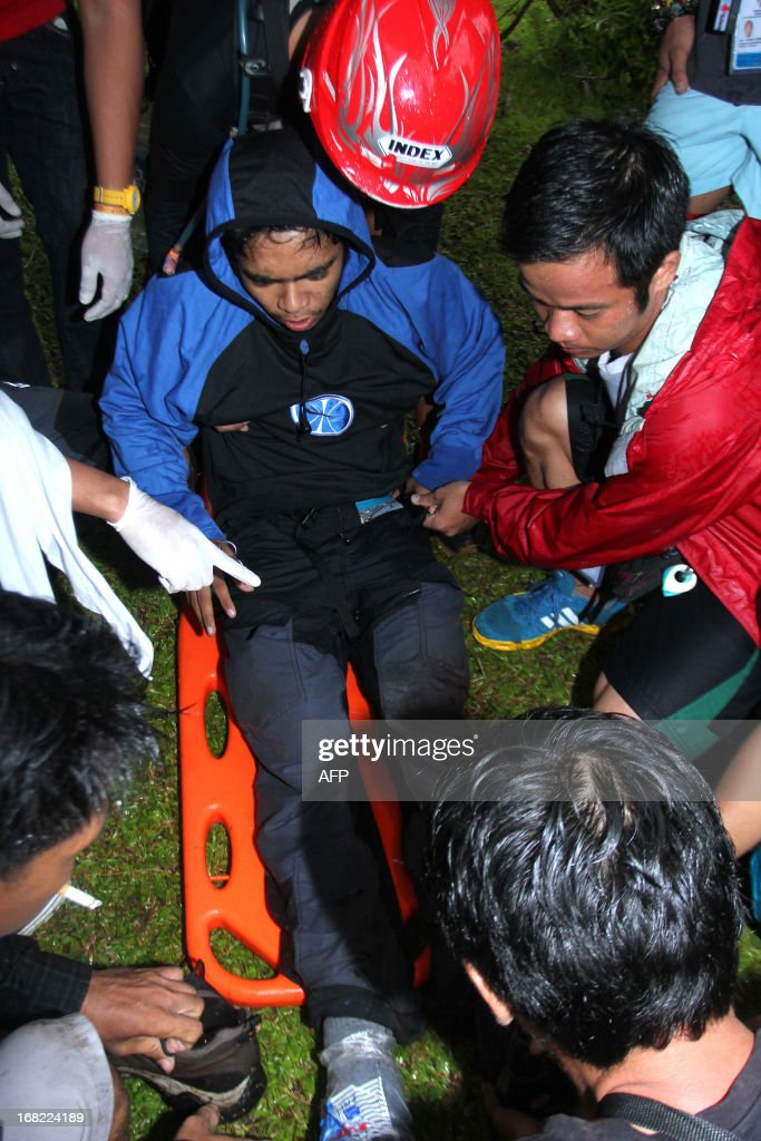 Nicanor Mabao Jr., one of the Filipino tour guides who survived after Mayon Volcano spewed a giant ash cloud, is placed on a stretcher from the slope of Mayon volcano in Legazpi city, Albay province, southeast of Manila on May 7, 2013. Three German tourists and their Filipino tour guide were crushed to death when one of the Philippines' most active volcanoes spewed a giant ash cloud and a hail of rocks on May 7, authorities said. AFP PHOTO/Jay-R Zuniga