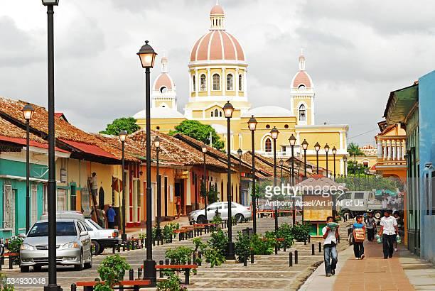 Nicaragua Granada children with school material on Calle La Calzada and Cathedral de Granada on the background
