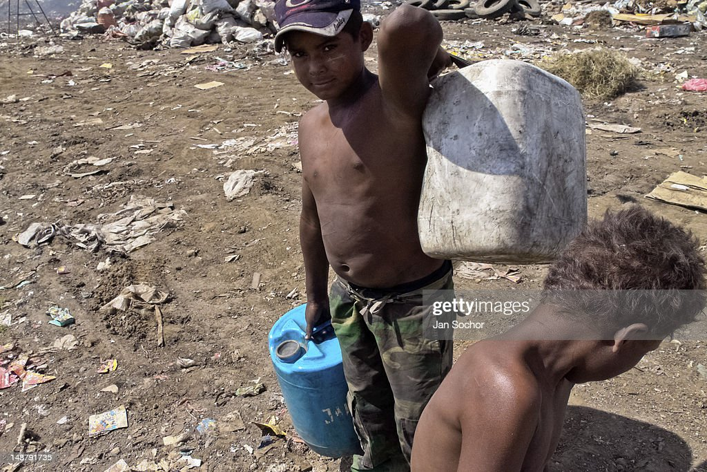 A Nicaraguan boy carries barrels of contaminated water for drinking in the garbage dump La Chureca on 09 November 2004 in Managua, Nicaragua. La Chureca is the biggest garbage dump in Central America, it is a lively sewer of Managua, the capital of Nicaragua. This dumping ground lies on the shores of the contaminated lake Xolotlán. Hundreds of human trash recyclers search in tons of smouldering garbage mainly metals (copper, aluminium), others concentrate on glass which is cheap, but in bigger amount. The majority of the searchers are families with children for whom recycling is a regular job. The children very often eat the food they find on the dump, none of them goes to school, they suffer from skin diseases, they have high levels of lead and DDT in blood. Many of them sniff glue, the drug of the poorest. The inhabitants of Managua say that there is the end of the world in Nicaragua – it is called La Chureca.