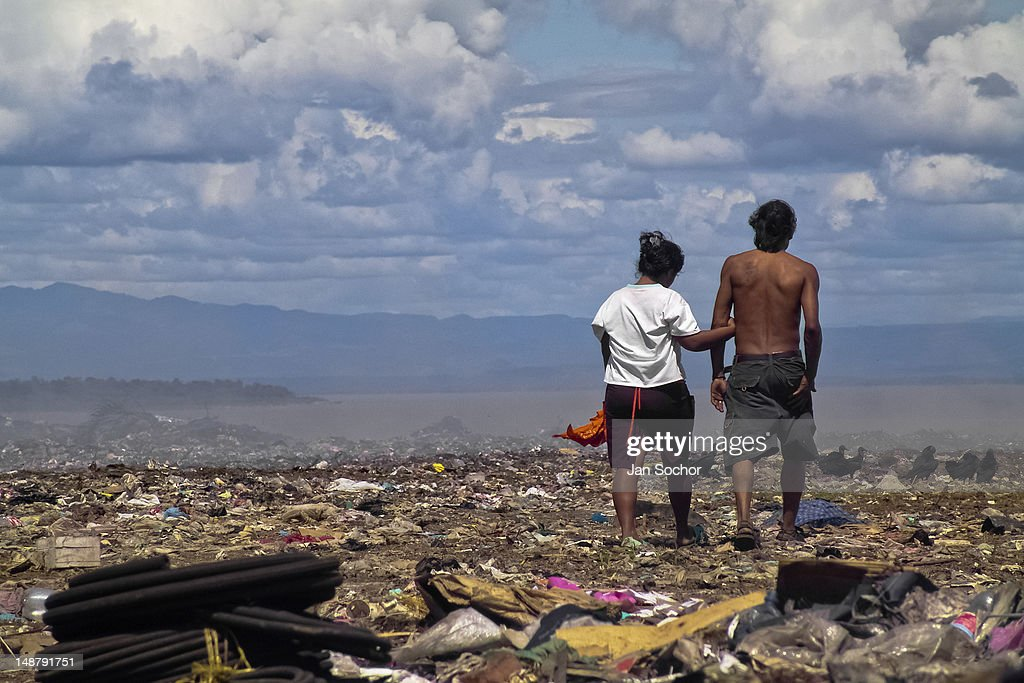 A Nicaraguan couple of garbage recollectors walks in the garbage dump La Chureca on 4 November 2004 in Managua, Nicaragua. La Chureca is the biggest garbage dump in Central America, it is a lively sewer of Managua, the capital of Nicaragua. This dumping ground lies on the shores of the contaminated lake Xolotlán. Hundreds of human trash recyclers search in tons of smouldering garbage mainly metals (copper, aluminium), others concentrate on glass which is cheap, but in bigger amount. The majority of the searchers are families with children for whom recycling is a regular job. The children very often eat the food they find on the dump, none of them goes to school, they suffer from skin diseases, they have high levels of lead and DDT in blood. Many of them sniff glue, the drug of the poorest. The inhabitants of Managua say that there is the end of the world in Nicaragua – it is called La Chureca.