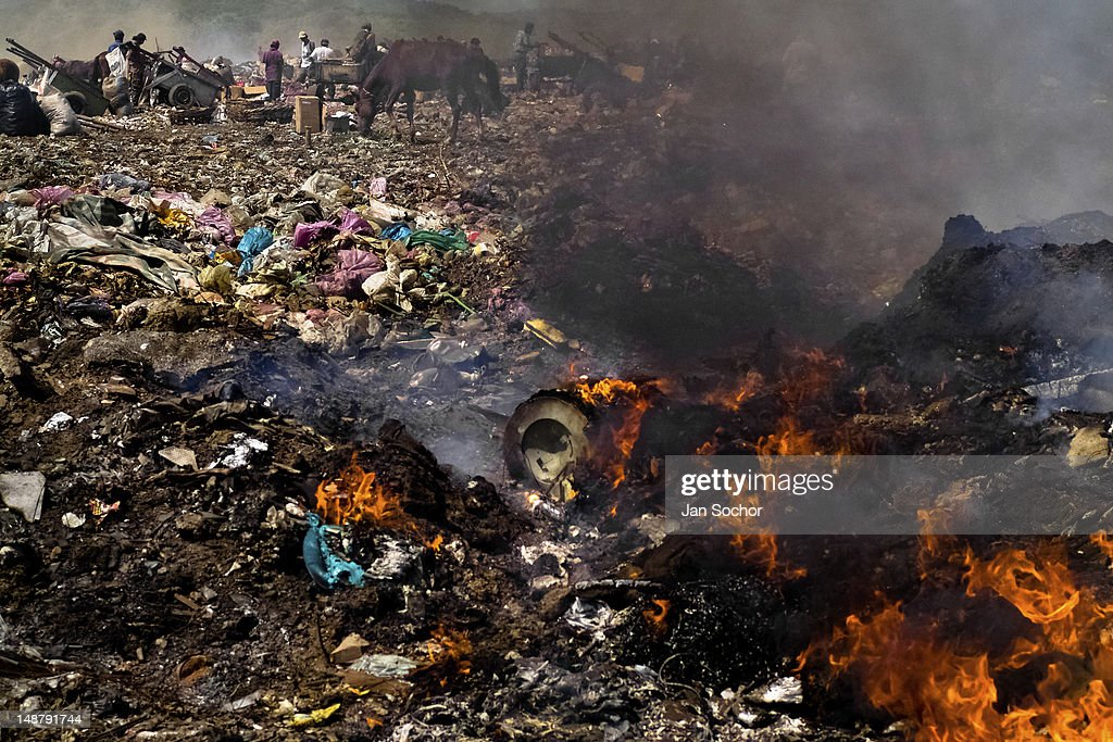 Nicaraguan garbage recollectors work among the burning piles of garbage in the garbage dump La Chureca on 09 November 2004 in Managua, Nicaragua. La Chureca is the biggest garbage dump in Central America, it is a lively sewer of Managua, the capital of Nicaragua. This dumping ground lies on the shores of the contaminated lake Xolotlán. Hundreds of human trash recyclers search in tons of smouldering garbage mainly metals (copper, aluminium), others concentrate on glass which is cheap, but in bigger amount. The majority of the searchers are families with children for whom recycling is a regular job. The children very often eat the food they find on the dump, none of them goes to school, they suffer from skin diseases, they have high levels of lead and DDT in blood. Many of them sniff glue, the drug of the poorest. The inhabitants of Managua say that there is the end of the world in Nicaragua – it is called La Chureca.