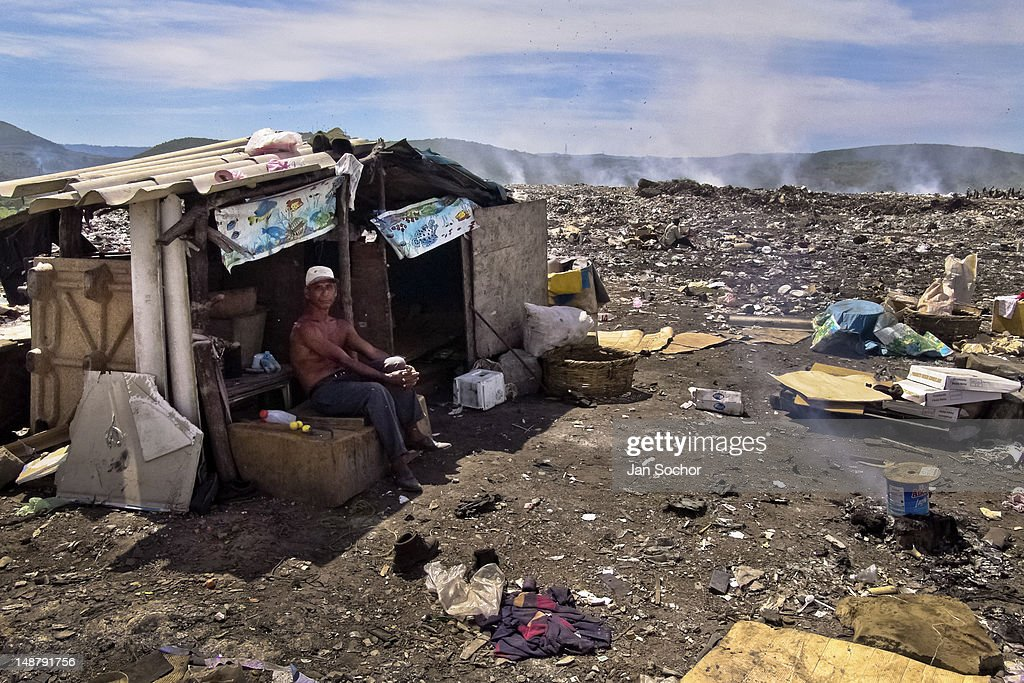A Nicaraguan man, a garbage recollector, lives in a shack in the garbage dump La Chureca, on 9 November, 2004 in Managua, Nicaragua. La Chureca is the biggest garbage dump in Central America, it is a lively sewer of Managua, the capital of Nicaragua. This dumping ground lies on the shores of the contaminated lake Xolotlán. Hundreds of human trash recyclers search in tons of smouldering garbage mainly metals (copper, aluminium), others concentrate on glass which is cheap, but in bigger amount. The majority of the searchers are families with children for whom recycling is a regular job. The children very often eat the food they find on the dump, none of them goes to school, they suffer from skin diseases, they have high levels of lead and DDT in blood. Many of them sniff glue, the drug of the poorest. The inhabitants of Managua say that there is the end of the world in Nicaragua – it is called La Chureca.