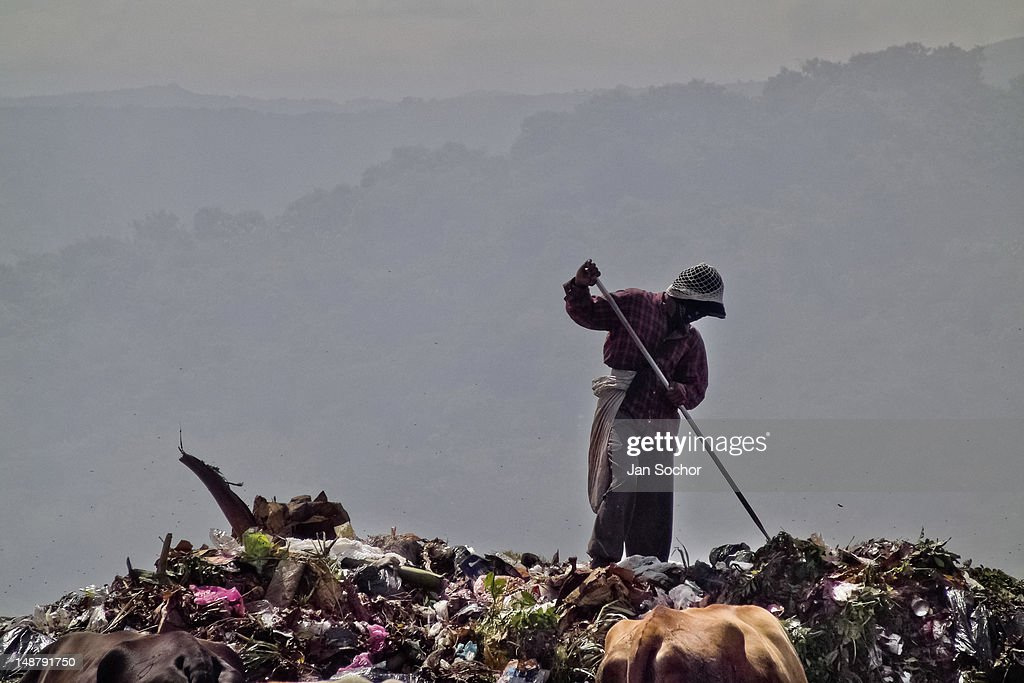 A Nicaraguan man recollects trash for recycling in the garbage dump La Chureca on 4 November 2004 in Managua, Nicaragua. La Chureca is the biggest garbage dump in Central America, it is a lively sewer of Managua, the capital of Nicaragua. This dumping ground lies on the shores of the contaminated lake Xolotlán. Hundreds of human trash recyclers search in tons of smouldering garbage mainly metals (copper, aluminium), others concentrate on glass which is cheap, but in bigger amount. The majority of the searchers are families with children for whom recycling is a regular job. The children very often eat the food they find on the dump, none of them goes to school, they suffer from skin diseases, they have high levels of lead and DDT in blood. Many of them sniff glue, the drug of the poorest. The inhabitants of Managua say that there is the end of the world in Nicaragua – it is called La Chureca.