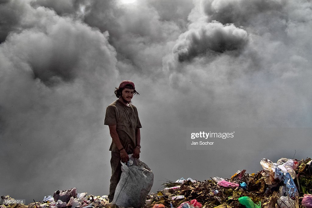 A Nicaraguan man searches for meat in a bloody pile of thrown intestines in the garbage dump La Chureca, Managua, Nicaragua, 10 November 2004. La Chureca is the biggest garbage dump in Central America, it is a lively sewer of Managua, the capital of Nicaragua. This dumping ground lies on the shores of the contaminated lake Xolotlán. Hundreds of human trash recyclers search in tons of smouldering garbage mainly metals (copper, aluminium), others concentrate on glass which is cheap, but in bigger amount. The majority of the searchers are families with children for whom recycling is a regular job. The children very often eat the food they find on the dump, none of them goes to school, they suffer from skin diseases, they have high levels of lead and DDT in blood. Many of them sniff glue, the drug of the poorest. The inhabitants of Managua say that there is the end of the world in Nicaragua - it is called La Chureca.