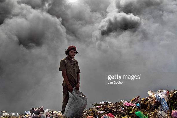 A Nicaraguan man searches for meat in a bloody pile of thrown intestines in the garbage dump La Chureca Managua Nicaragua 10 November 2004 La Chureca...