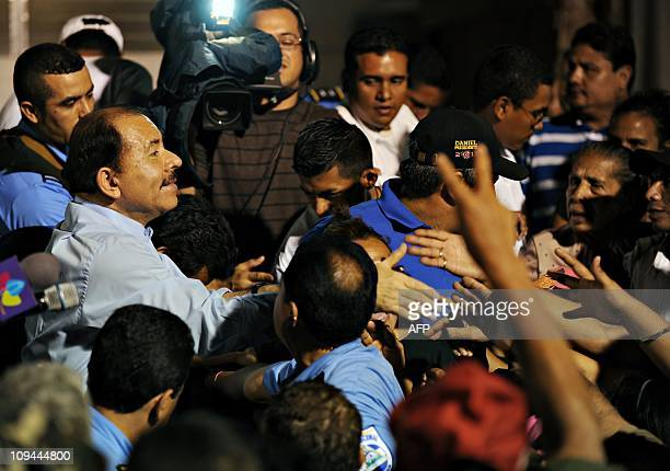 Nicaraguan President Daniel Ortega shakes hands of supporters as homes are delivered to Nicaraguan workers in Managua on February 25 2011 Ortega...