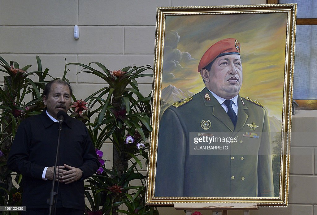Nicaraguan President Daniel Ortega speaks next to a portrait of former Venezuelan President Hugo Chavez before the opening of the Petrocaribe Summit, in Caracas on May 5, 2013. Pertocaribe is an alliance Venezuela has with several Caribbean states under which it supplies oil to them at cut-rate prices.
