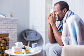 Seasonal cold. Nice handsome adult man sitting on the sofa and holding a paper tissue while sneezing