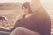 nice beautiful middle age 40 years old couple man and woman caucasian hugged and stay together on the beach sitting in the sand and enjoying a gold amazing sunset for nice leisure activity outdoor in