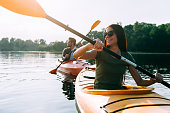 Beautiful young couple kayaking on lake together and smiling