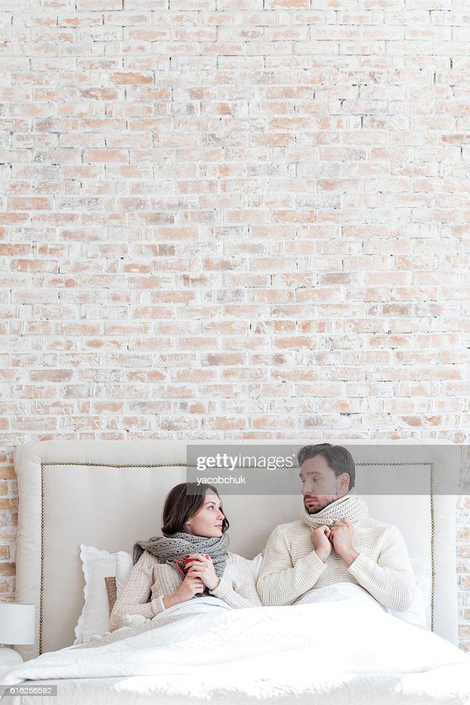 Nice depressed couple lying under the blanket : Foto de stock