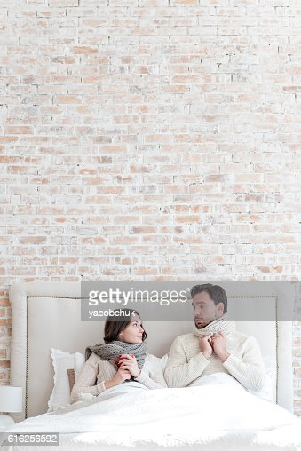 Nice depressed couple lying under the blanket : Foto de stock