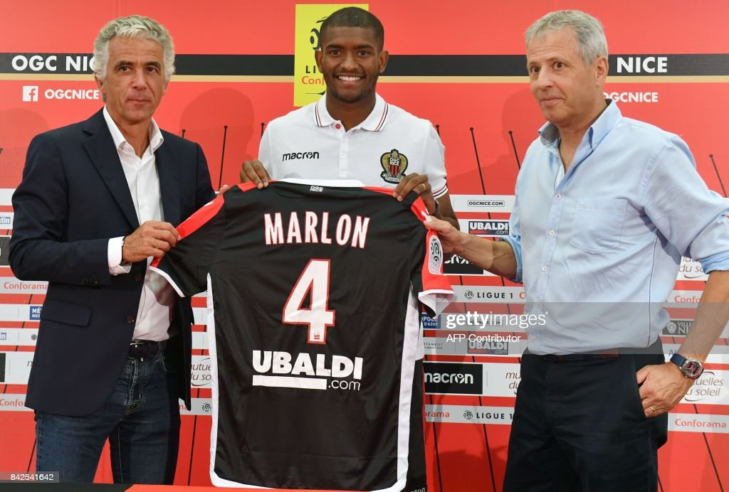 OGC Nice football club's new recruit Brazilian defender Santos Marlon poses with his new jersey between Swiss head coach Lucien Favre (R) and French President Jean-Pierre Rivere (L) during a press conference to present the club's new players on September 4, 2017 at the Allianz Riviera stadium in Nice, southeastern France. /