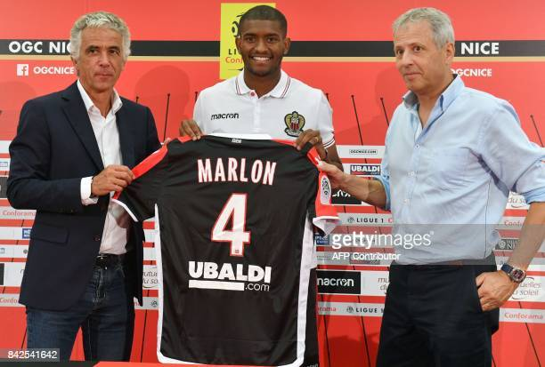 OGC Nice football club's new recruit Brazilian defender Santos Marlon poses with his new jersey between Swiss head coach Lucien Favre and French...