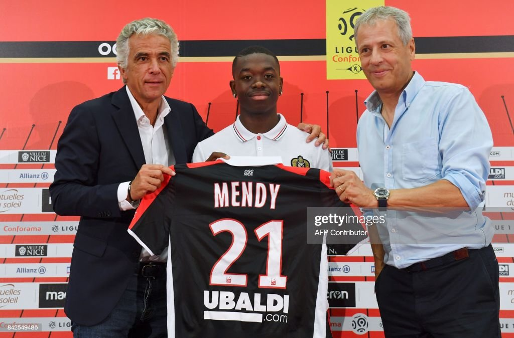 OGC Nice football club's new recruit French midfielder Nampalys Mendy (C) poses with his new jersey between Swiss head coach Lucien Favre (R) and French President Jean-Pierre Rivere (L) during a press conference to present the club's new players on September 4, 2017 at the Allianz Riviera stadium in Nice, southeastern France. /