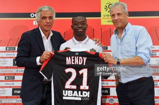 OGC Nice football club's new recruit French midfielder Nampalys Mendy poses with his new jersey between Swiss head coach Lucien Favre and French...